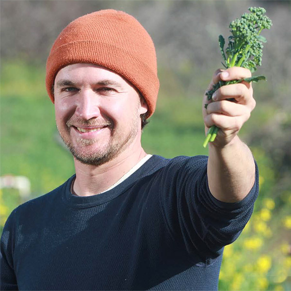 photo of an organic farmer in the field holding up a stalk of brocolli