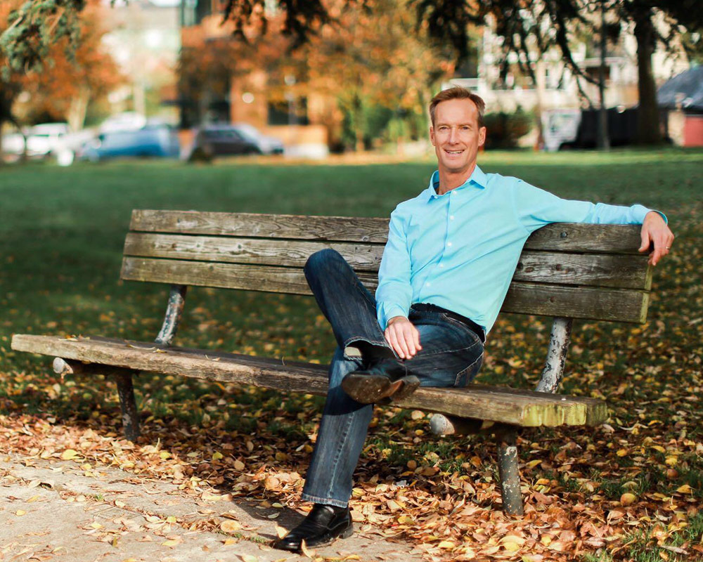 photo of Dr. Ramaley sitting on a park bench in Seattle