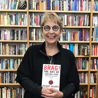 "Peggy Klaus holding her book ""Brag! The Art of Tooting Your Own Horn Without Blowing It"""