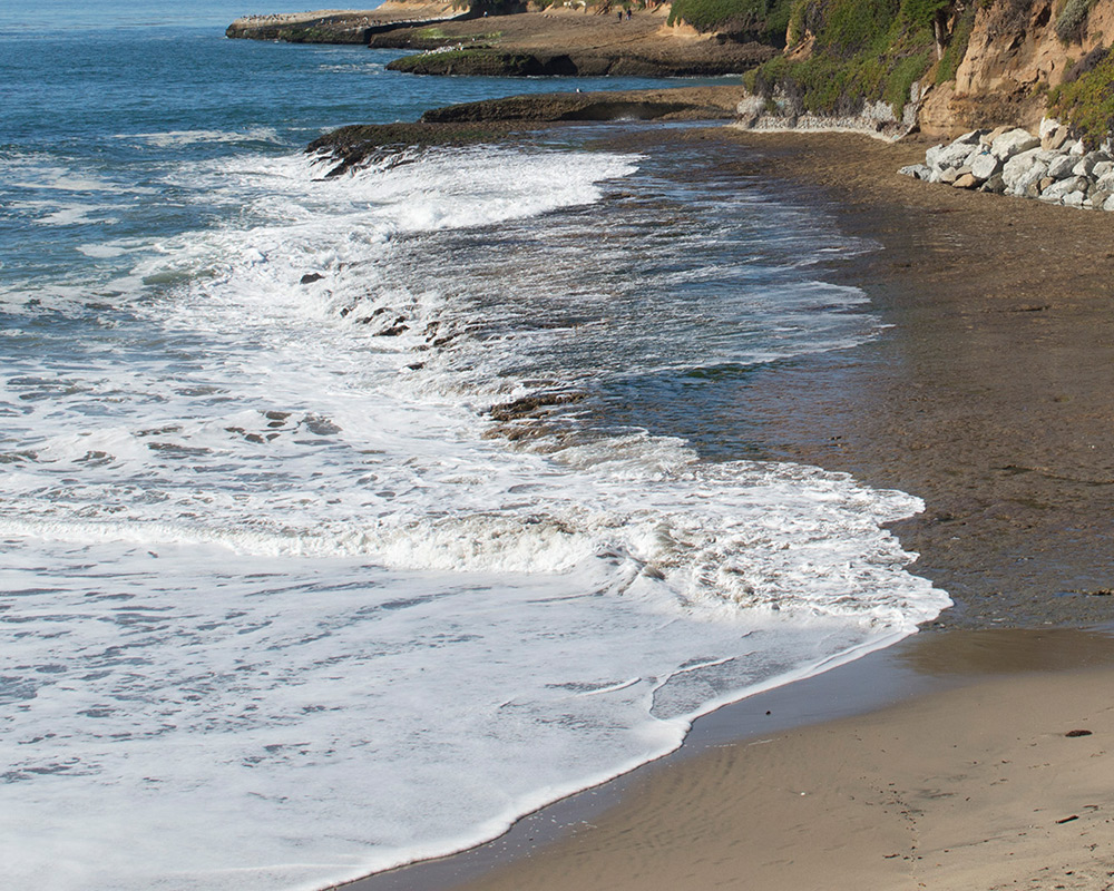 photo of waves lapping up at the shore on the CA coast