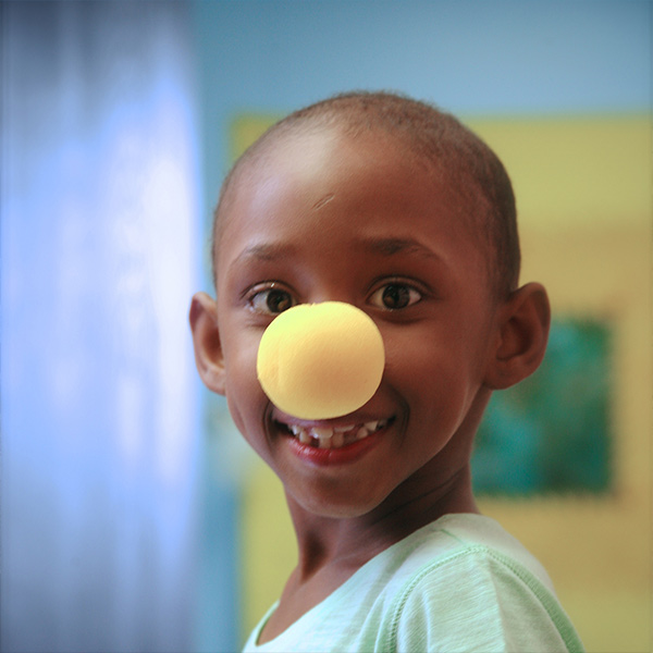 photo of a beautiful young girl with a clown nose